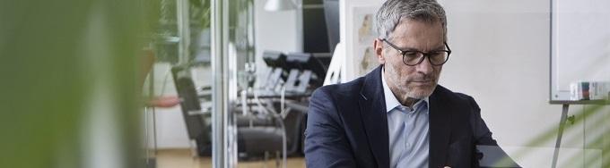 Successful businessman sitting in board room using digital tablet